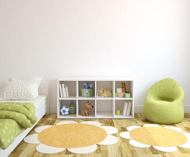 Chambre d'enfant avec un fauteuil vert et des tapis en forme de marguerites.