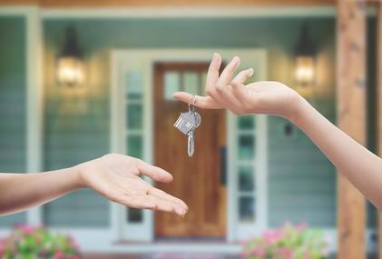 Deux mains s'échangent des clés.