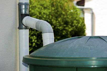 Récupérateur d'eau de pluie sous une gouttière.
